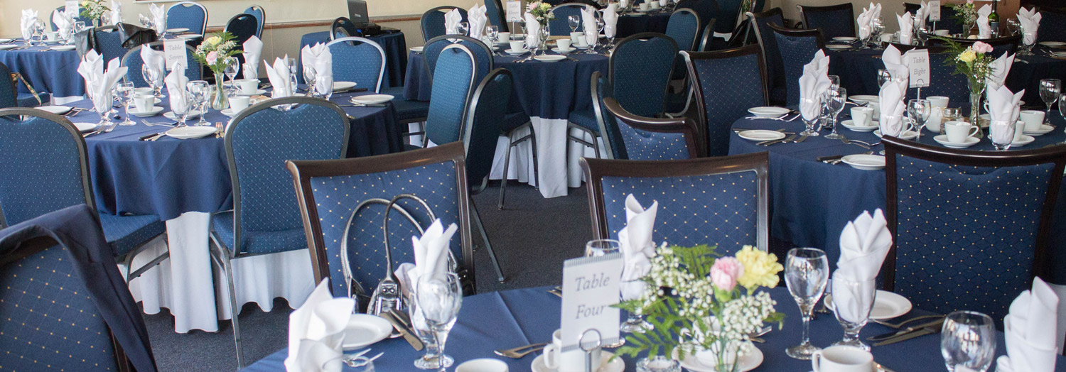 Dining tables setup with dinnerware and glassware. Pink and yellow flowers for the center piece. Navy coloured theme.