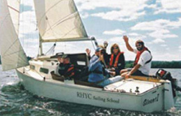 Group of people waving from a sailboat out on the lake.