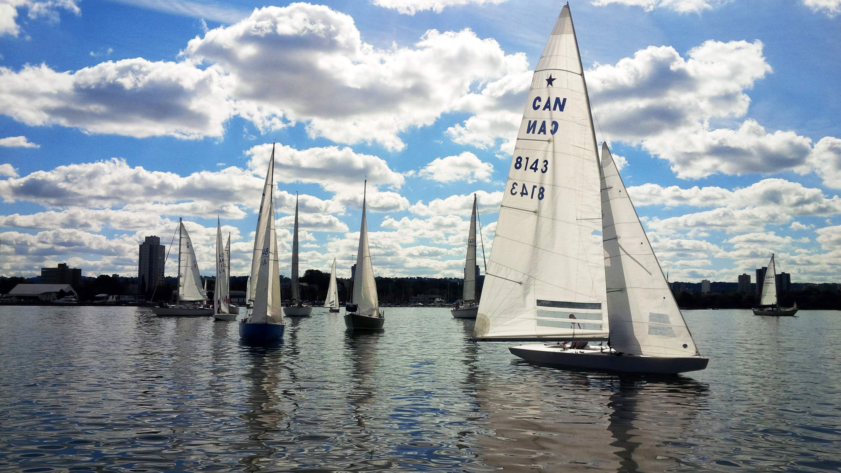 Sailboats at Royal Hamilton Yacht Club out on the lake. Sunny day with clouds.